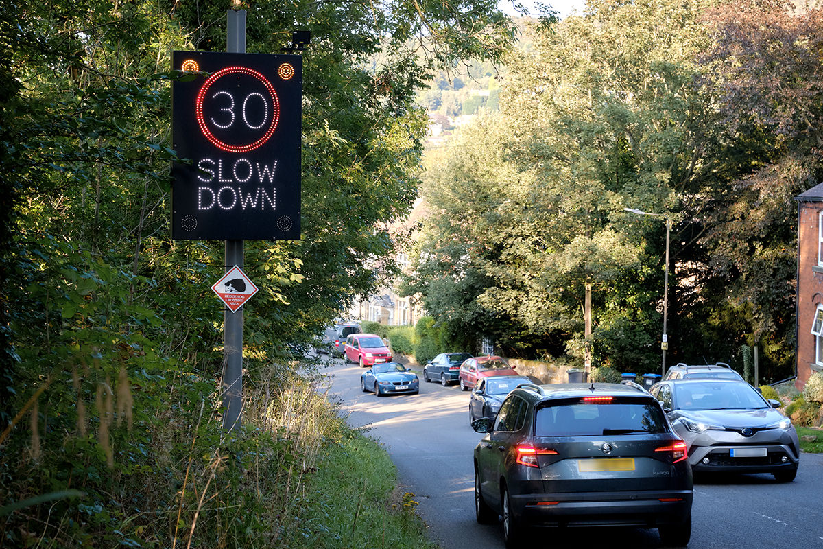 A car entering Grindleford, showing the speeding sign illuminated