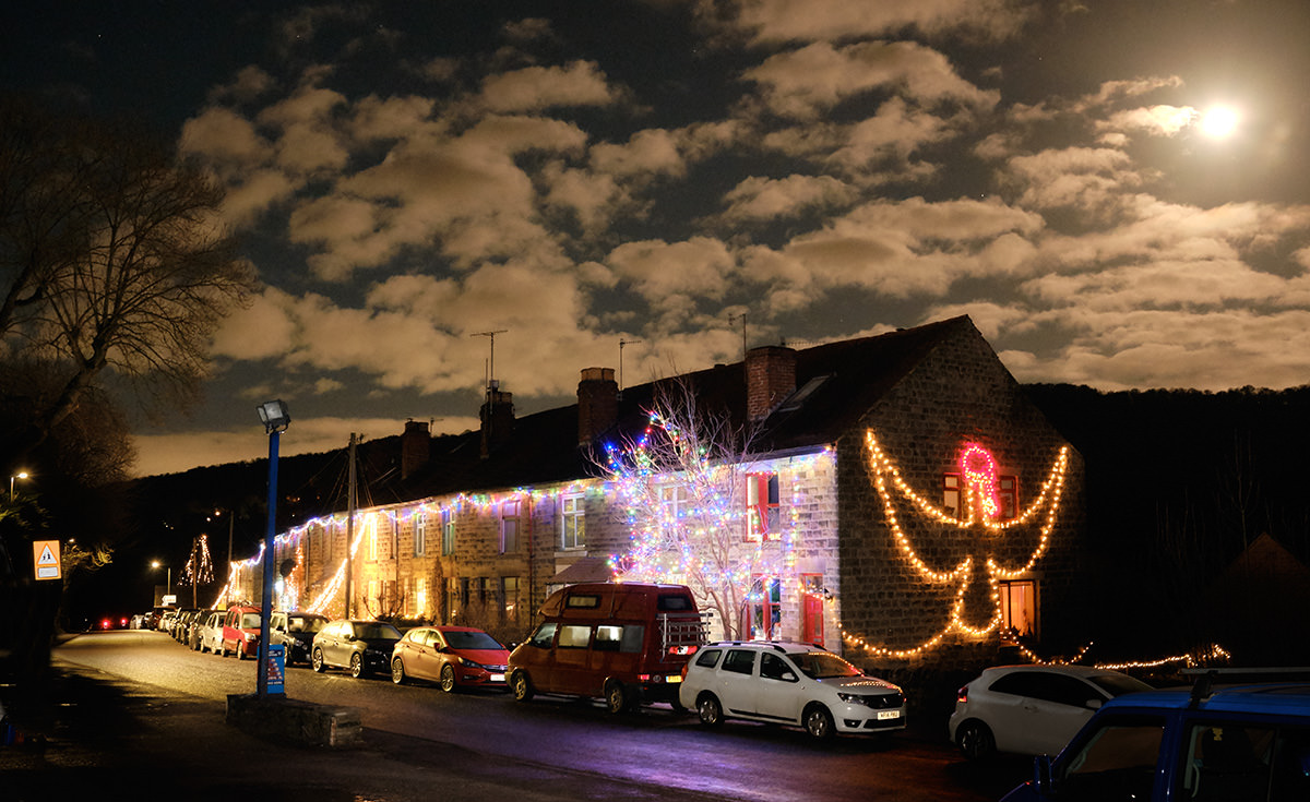 Night-time shot of a row of houses in Grindleford covered with Christmas lights.
